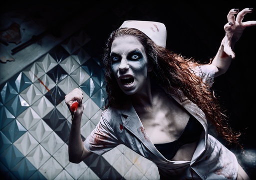 Horror shot: terrible evil crazy nurse (doctor) attacking by bloody syringe. Zombie woman (living dead). Monster from nightmare