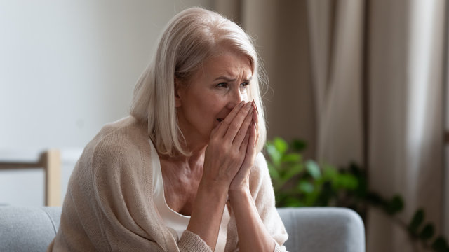 Upset mature woman crying, sitting alone, feeling lonely and unwell