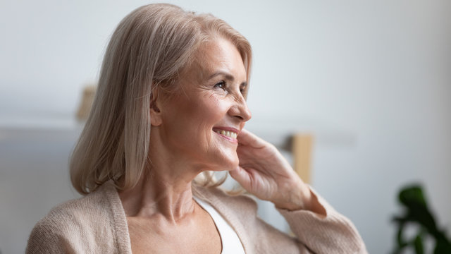 Close up profile smiling mature woman dreaming about good future