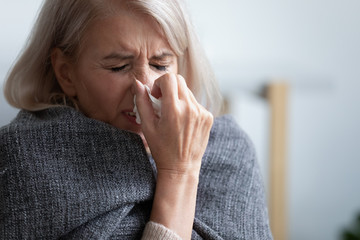 Unhappy mature woman covered blanket feeling bad, sneezing