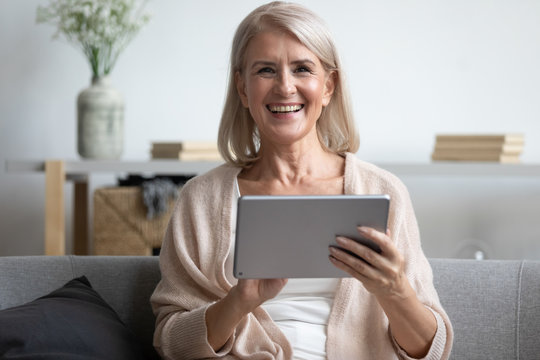 Happy mature woman using computer tablet, laughing at funny joke
