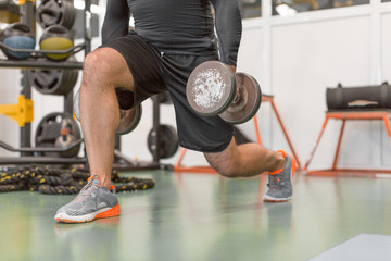 Cropped image of a man doing exercise for legs. Man working out legs with dumbbells.