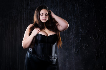 Sexy plus size model in black corset, fat woman with big natural breasts on dark background, body positive concept