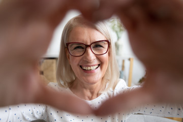 Portrait smiling mature woman looking through heart shaped hands