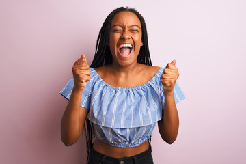African american woman wearing striped t-shirt standing over isolated pink background excited for success with arms raised and eyes closed celebrating victory smiling. Winner concept.