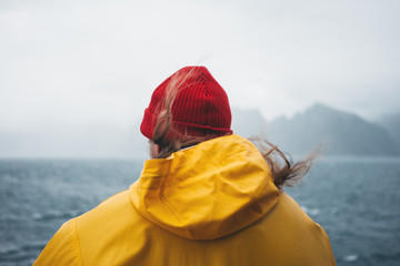 Alone traveler wearing yellow raincoat and red hat looking at stormy sea and foggy mountain. Lifestyle outdoor adventure, scandinavian wanderlust
