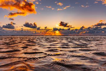 Photo sur Plexiglas La Mer du Nord Schöner Sonnenuntergang am Meer mit Wolken und Wasserspiegelung