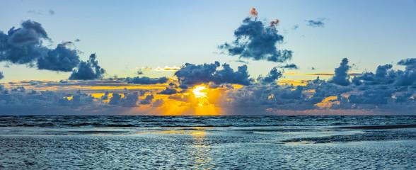 Fotobehang Noordzee Schöner Sonnenuntergang am Meer mit Wolken und Wasserspiegelung