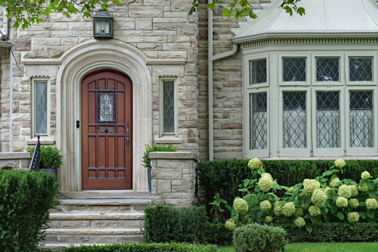 stone faced house with leaded glass windows and elegant wooden front door