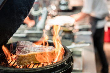 Close-up of a steak on a burning grill in the kitchen of a restaurant with high quality food