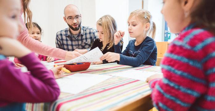 Preschool teachers and children in kindergarten