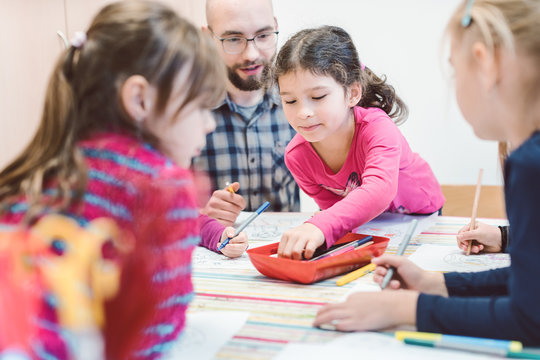 Male Kindergarten teacher with his group of children