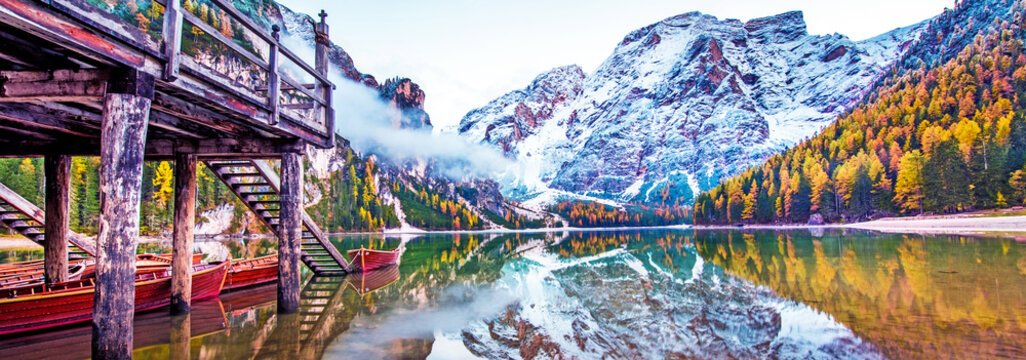 Magical beautiful fairy autumn landscape with boats on the lake on Fanes-Sennes-Braies natural park in the Dolomites in South Tyrol, Alps, Italy, Europe. Exotic amazing places. (harmony - concept)