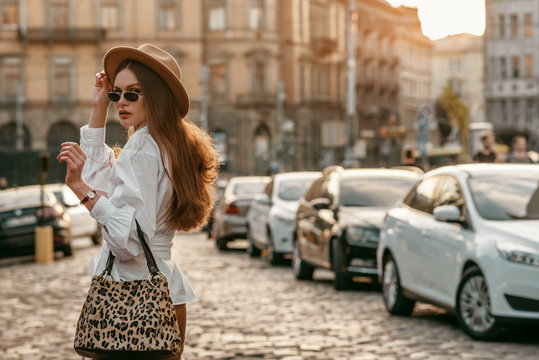 Outdoor fashion portrait of elegant, luxury woman wearing beige hat, sunglasses, trendy white shirt, brown wrist watch, holding animal, leopard print bag, walking in street. Copy, empty space for text