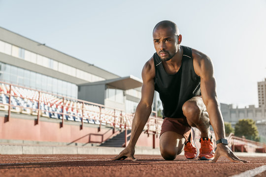 Low angle view of young man athlete in starting position for running on sports track