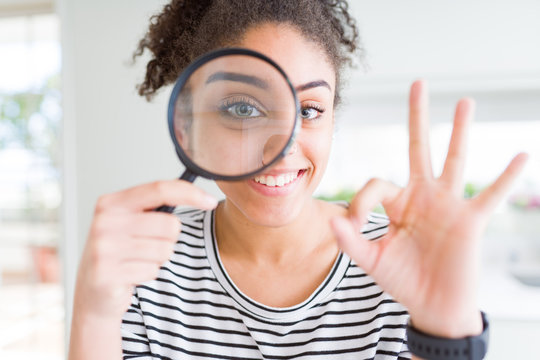 Young african american woman looking through magnifying glass doing ok sign with fingers, excellent symbol