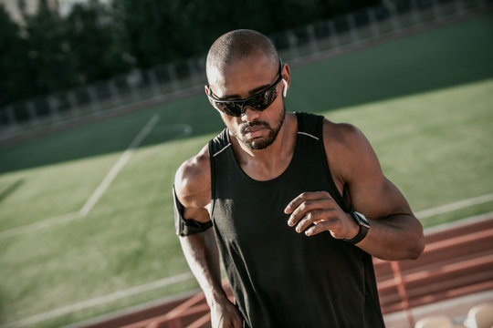 Close up of male athlete in sunglasses and earphones running up the stairs of a stadium