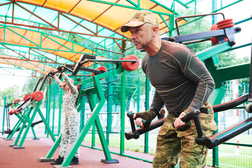 outdoors training. man and woman workouts on weight machine in military clothing