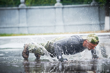 outdoors training. man doing push up on wet place in military clothing