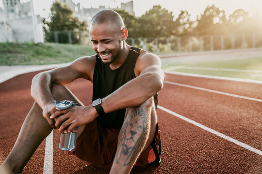 Cheerful young sporty man sitting on stadium running track with bottle of water in hands