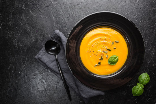 Vegetarian autumn pumpkin cream soup with seeds on dark background, top view