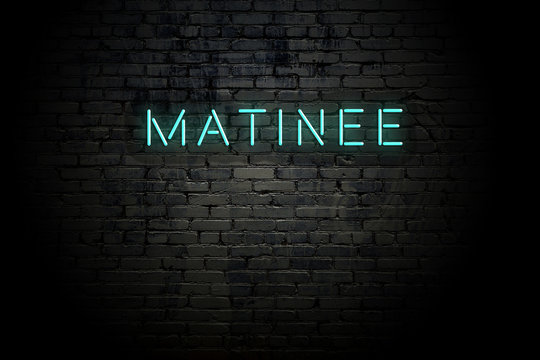 Highlighted brick wall with neon inscription matinee