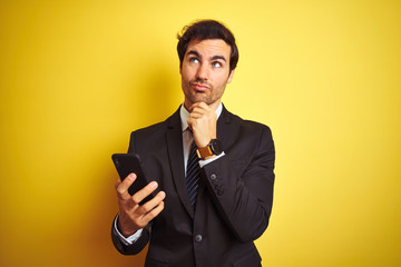 Young handsome businessman using smartphone standing over isolated yellow background serious face thinking about question, very confused idea