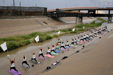People practice yoga at the Rio Grande at the border between Mexico and U.S with the purpose of sending a signal to change the international perspective of the border, in Ciudad Juarez