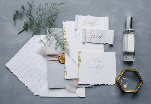 Wedding details flat lay. Wedding invitation and scroll paper. Bottle with fragrance. Ring box. Simple bouquet.