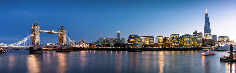 Fotomurales - Die beleuchtete Skyline von London am Abend mit Tower Bridge und modernen Bürogebäuden, Großbritannien