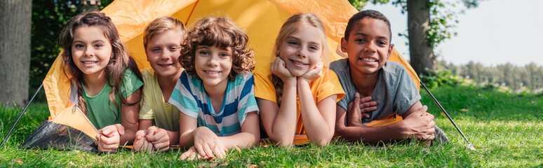 Poster Camping panoramic shot of happy multicultural kids smiling while lying near camp