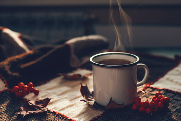 Wall Murals Coffee beans Hot steaming cup of coffee or tea with fall leaves and spices on a warm plaid on a bright Sunny day. Autumn mood.