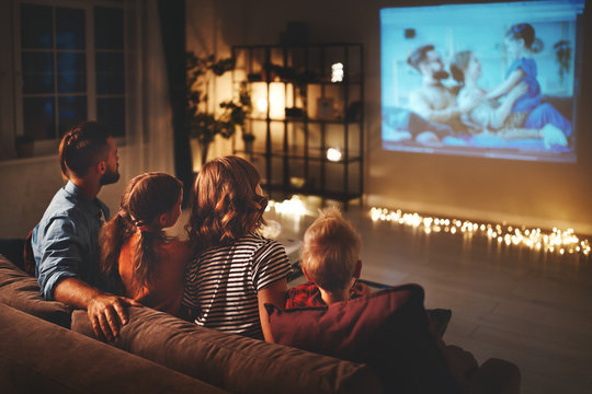 family mother father and children watching projector, TV, movies with popcorn in   evening   at home.