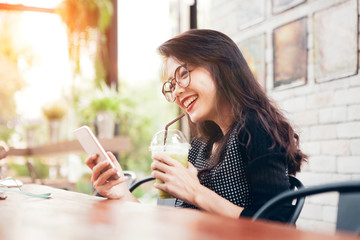 beautiful asian younger woman drinking cool green tea in bottle and looking on mobilephone screen with happiness face