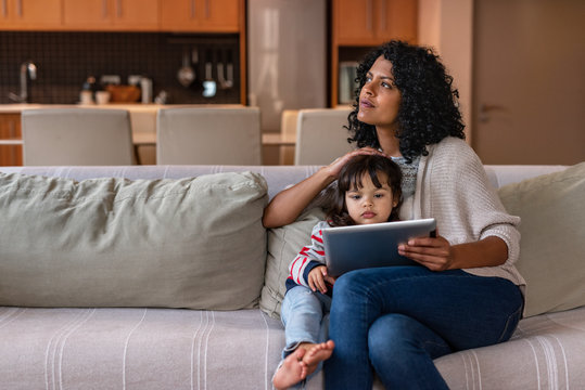 Mother using a tablet with her little daughter at home