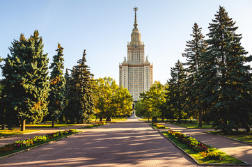 Main building of Moscow state university or MSU and close perspective of monument to greatest russian scientist Lomonosov with autumn trees and falling leaves. Education in Russia, Moscow.