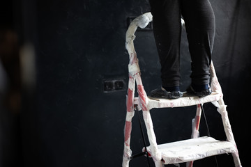 Close-up of legs on red steel ladder on background on black wall of apartment in time of repair.