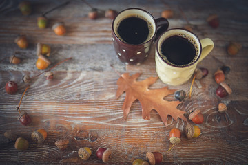Two coffee sitting on an old log by an outdoor campfire. Selective focus on mug with blurred background. Camping. Autumn acorns background