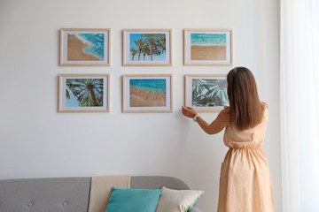 Female interior designer decorating white wall with pictures indoors