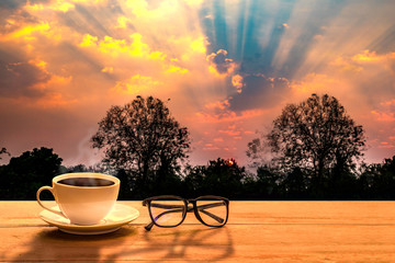 a selective focus picture of a cup of coffee with eye glass on wooden table with sky clouds and  tree in the evening sunset