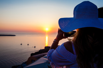 SANTORINI, GREECE - APRIL, 2018: Young woman looking at the beautiful sunset at the famous Caldera of Santorini Island in Oia City