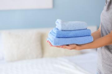Female housekeeper with clean towels in bedroom