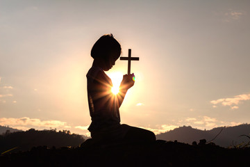 Silhouette child praying to the GOD while holding a crucifix symbol with bright sunbeam on the sky