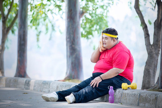 Overweight man resting after exercise in the park