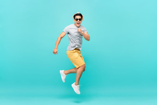 Amazed handsome Asian tourist man jumping