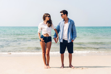 Romantic lovers young couple relaxing together on the tropical beach.Man holding hand with woman and enjoy life.Summer vacations
