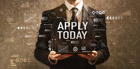 Apply today with businessman holding a tablet computer on a dark vintage background