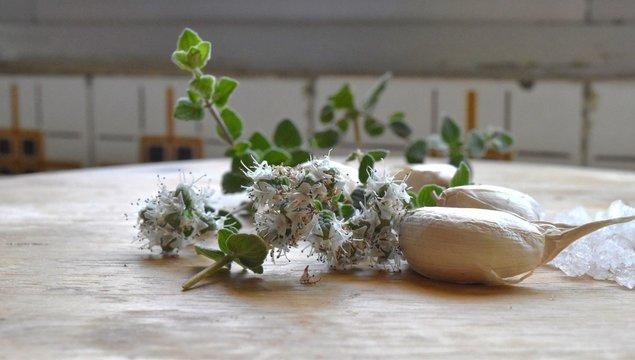 garlic and zaatar (origanum syriacum) biblical hyssop on a wooden cutting board