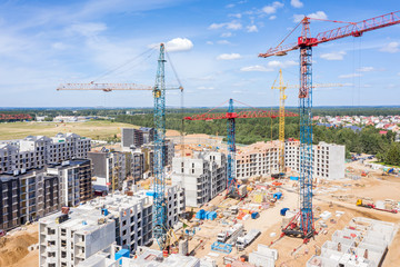aerial panoramic image of city construction site against blue sky background
