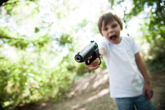 weapon control concept of aggressive shouting child threatens with real gun in USA outdoor park